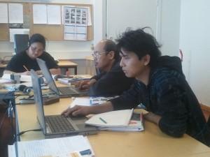 I klasserommet. James, Aung Gyi og Mogapo les rapport for veke 11