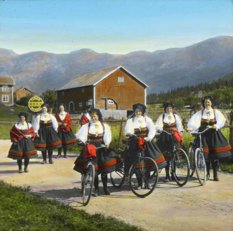 Åtte kvinner i Setesdalsdrakt på veg til Valle kyrkje (fire med sykkel). Dei fire syklistane er (f.v.): Tone Rygnestad, Gunhild Dale, Gyro O. Haugen og Gyro T. Rygnestad. A.B. Wilse 1934/ Norsk Teknisk Museum