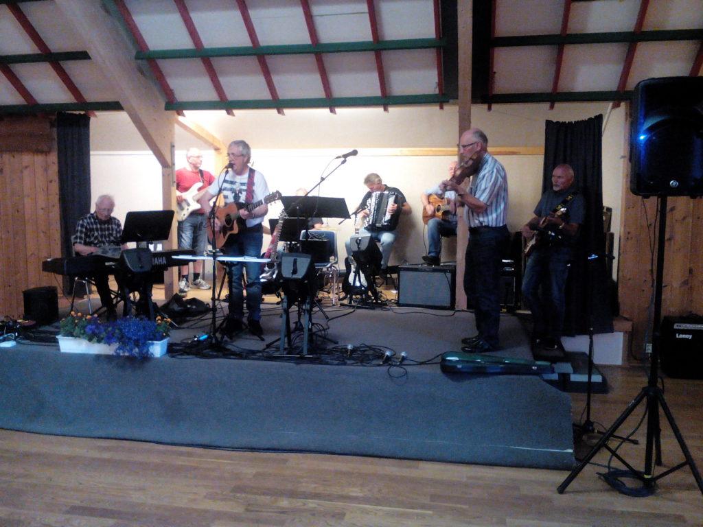 Oddvar med musikarar på scenen på Ose grendehus. Foto: Harald Haugland